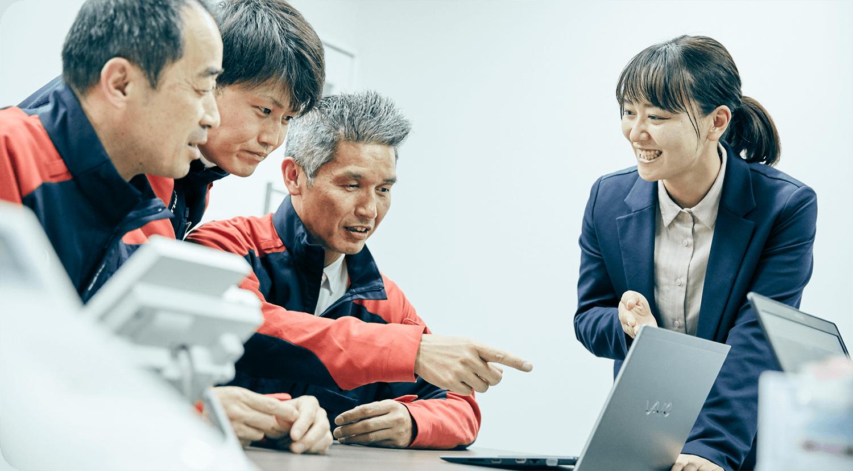 成田さんがノートパソコンを持って現場の人と話すシーン